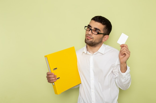 Vorderansicht des männlichen büroangestellten im weißen hemd, das karte und dateien auf grüner wand hält