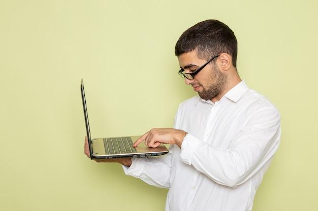 Vorderansicht des männlichen büroangestellten im weißen hemd, das laptop auf hellgrüner wand hält
