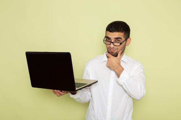 Vorderansicht des männlichen büroangestellten im weißen hemd, das laptop-denken an der hellgrünen wand hält und verwendet
