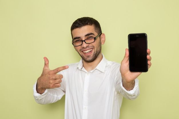 Vorderansicht des männlichen büroangestellten im weißen hemd, das sein telefon hält, das auf grüner wand lächelt