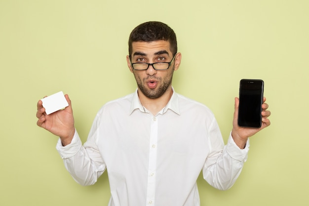 Vorderansicht des männlichen büroangestellten im weißen hemd, das telefon und karte an der grünen wand hält