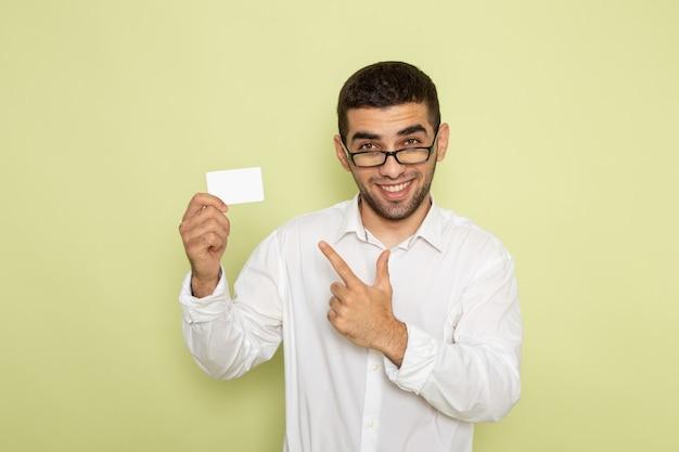 Vorderansicht des männlichen büroangestellten im weißen hemd, das weiße plastikkarte an der hellgrünen wand hält