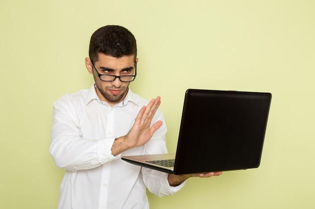 Vorderansicht des männlichen büroangestellten im weißen hemd unter verwendung des laptops auf grüner wand