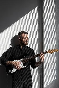 Vorderansicht des männlichen darstellers, der neben fenster beim spielen der e-gitarre aufwirft