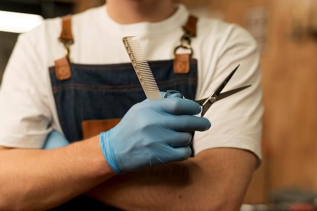 Vorderansicht des männlichen friseurs, der eine schere im friseursalon hält