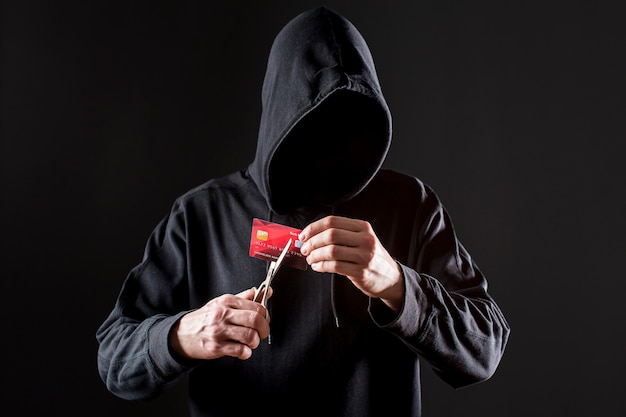 Vorderansicht des männlichen hackers, der kreditkarte mit schere schneidet