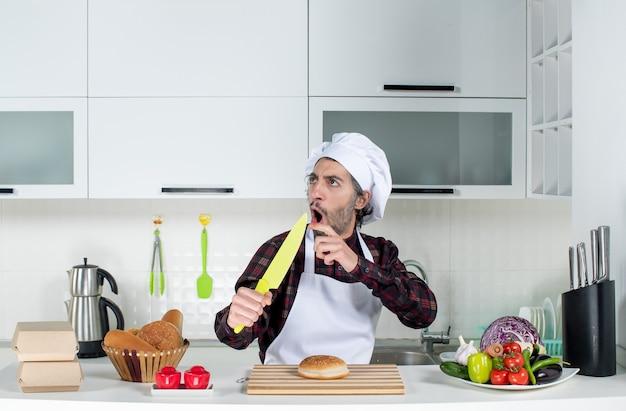 Vorderansicht des männlichen kochs, der auf das messer in der küche zeigt