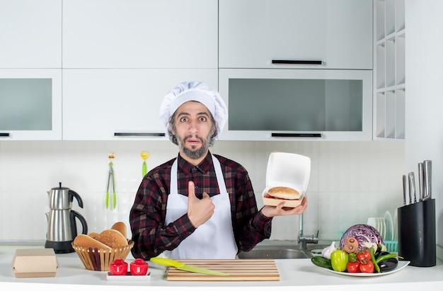Vorderansicht des männlichen kochs, der auf sich selbst zeigt und verkaufsschild und burger in der küche hält