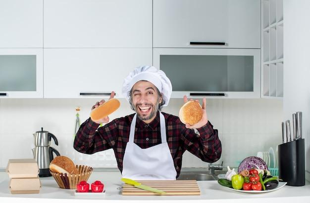 Vorderansicht des männlichen kochs, der brot in beiden händen in der küche hält