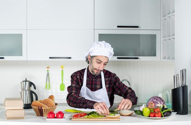 Vorderansicht des männlichen kochs, der burger in der küche macht
