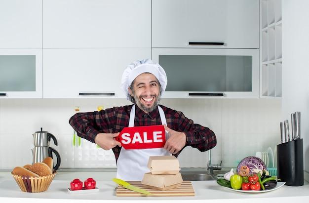 Vorderansicht des männlichen kochs, der das verkaufsschild in der küche hält