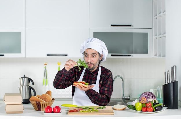 Vorderansicht des männlichen kochs, der dem burger hinter dem küchentisch grün hinzufügt