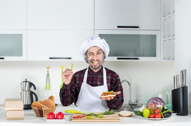 Vorderansicht des männlichen kochs, der dem burger pfeffer hinzufügt, der hinter dem küchentisch steht