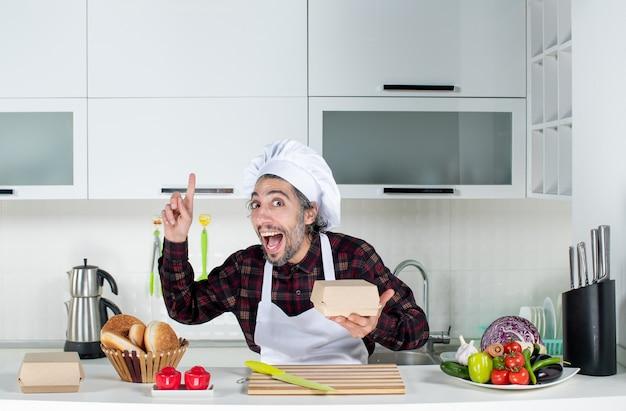 Vorderansicht des männlichen kochs, der eine box hält, die mit dem finger nach oben zeigt, der hinter dem küchentisch in der küche steht