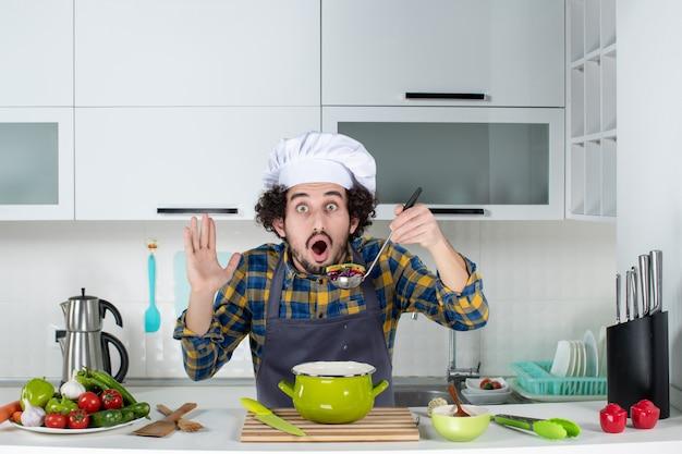 Vorderansicht des männlichen kochs, der frisches gemüse kocht, das fertiggerichte schmeckt und sich in der weißen küche schockiert fühlt