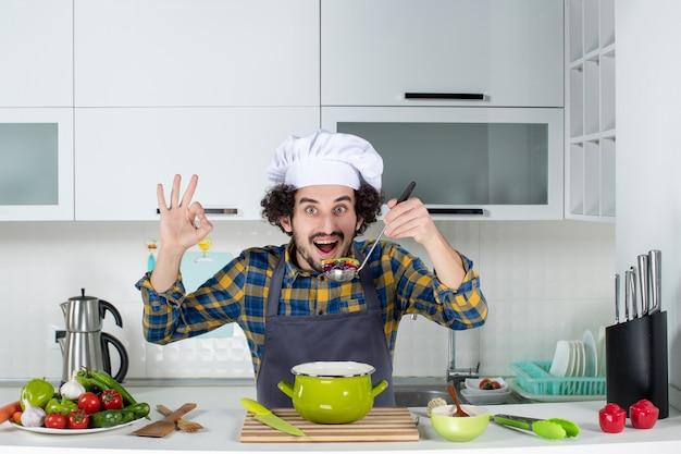 Vorderansicht des männlichen kochs, der frisches gemüse kocht, das fertiggerichte verkostet und in der weißen küche eine brillengeste macht