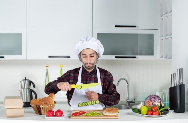 Vorderansicht des männlichen kochs, der gemüse in der küche schneidet