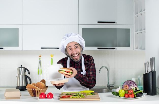 Vorderansicht des männlichen kochs, der großen burger aus der kiste nimmt, die hinter dem küchentisch steht