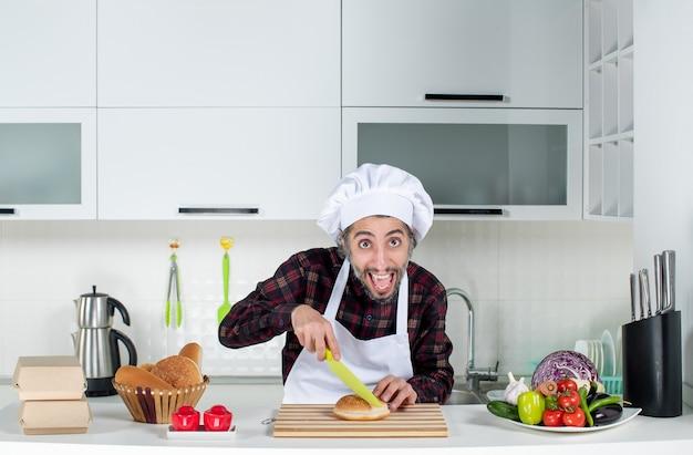 Vorderansicht des männlichen kochs, der in der küche brot auf holzbrett schneidet