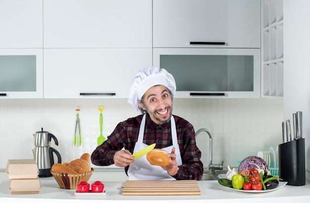 Vorderansicht des männlichen kochs, der in der küche brot mit gelbem messer schneidet