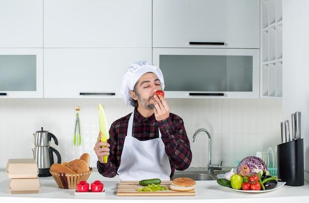 Vorderansicht des männlichen kochs, der in der küche nach tomaten riecht