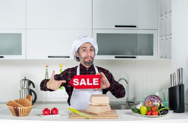 Vorderansicht des männlichen kochs, der mit dem finger selbst zeigt, der das verkaufsschild in der küche hochhält
