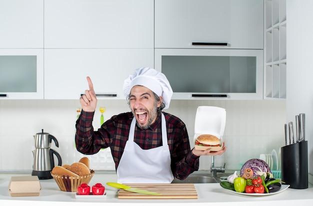 Vorderansicht des männlichen kochs, der mit einem blinzelnden auge einen burger hält und auf die decke in der küche zeigt