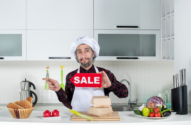 Vorderansicht des männlichen kochs, der nach links zeigt und das verkaufsschild in der küche hochhält