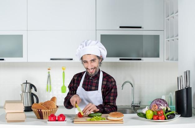 Vorderansicht des männlichen kochs, der tomaten in der küche hackt