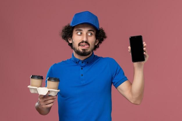 Vorderansicht des männlichen kuriers in blauer uniform und kappe mit kaffeetassen und arbeitstelefon auf seinen händen