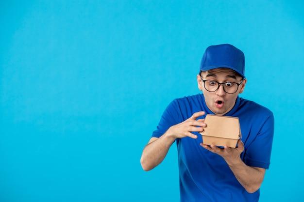 Vorderansicht des männlichen kuriers in der blauen uniform mit der kleinen nahrungsverpackung auf blau