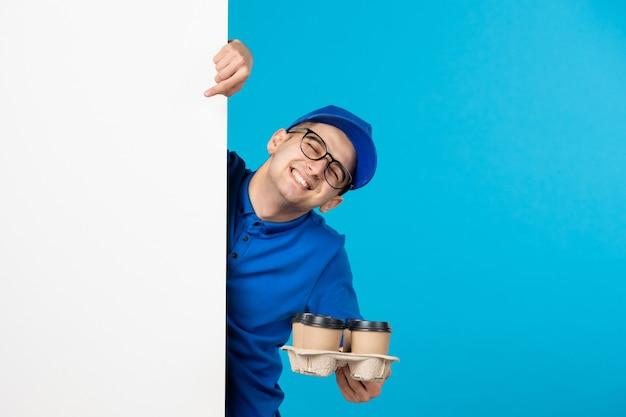Vorderansicht des männlichen kuriers in der blauen uniform mit kaffee auf dem blau