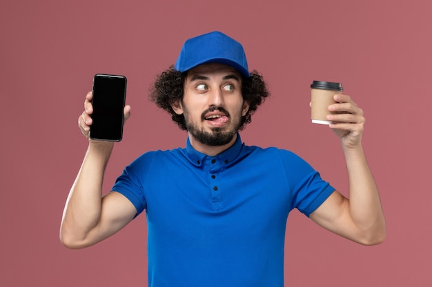 Vorderansicht des männlichen kuriers in der blauen uniform und in der kappe mit der kaffeetasse und dem telefon der lieferung auf seinen händen auf der rosa wand