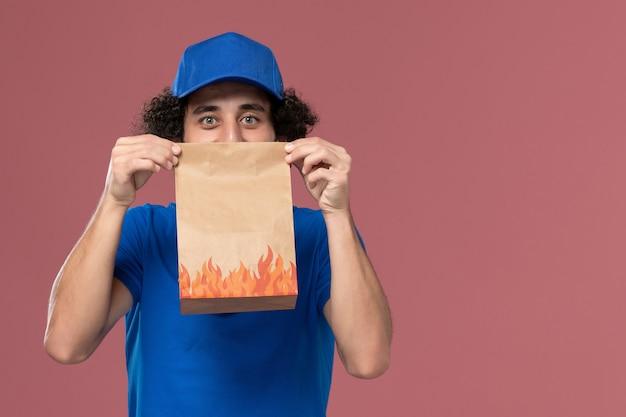 Vorderansicht des männlichen kuriers in der blauen uniformkappe mit dem lebensmittelpaket des lieferpapiers auf seinen händen auf der hellrosa wand