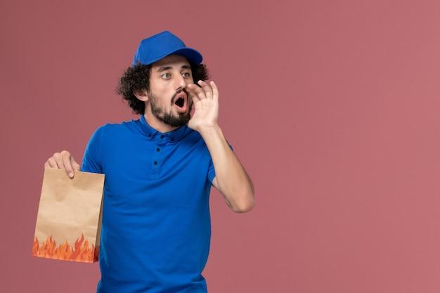 Vorderansicht des männlichen kuriers in der blauen uniformkappe mit der lebensmittelverpackung des lieferpapiers auf seinen händen, die auf der hellrosa wand rufen