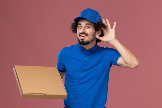 Vorderansicht des männlichen kuriers in der blauen uniformkappe mit nahrungsmittelbox auf seinen händen auf hellrosa wand