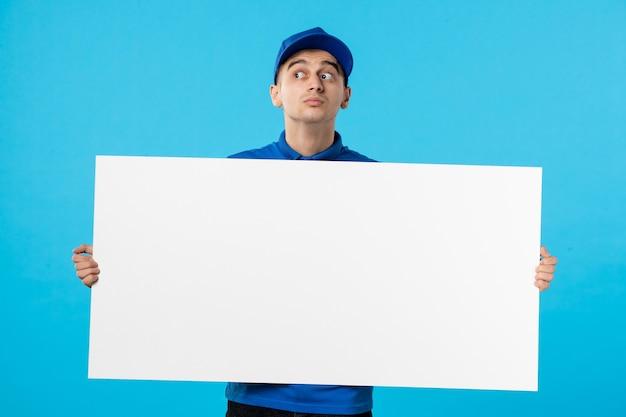 Vorderansicht des männlichen kuriers in uniform mit weißem einfachem schreibtisch auf blau