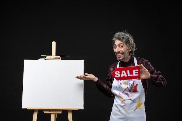 Vorderansicht des männlichen malers mit staffelei mit verkaufsbanner an dunkler wand