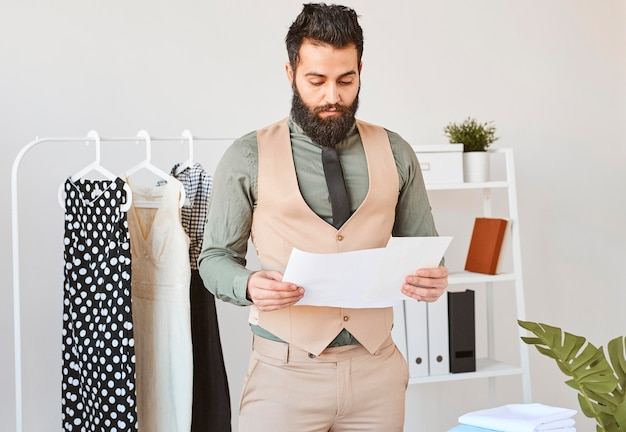 Vorderansicht des männlichen modedesigners, der im atelier mit papieren arbeitet