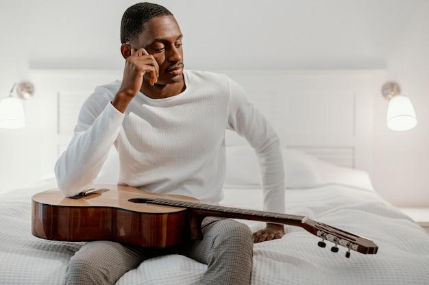 Vorderansicht des männlichen musikers auf dem bett mit gitarre