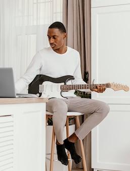 Vorderansicht des männlichen musikers, der e-gitarre spielt und laptop verwendet