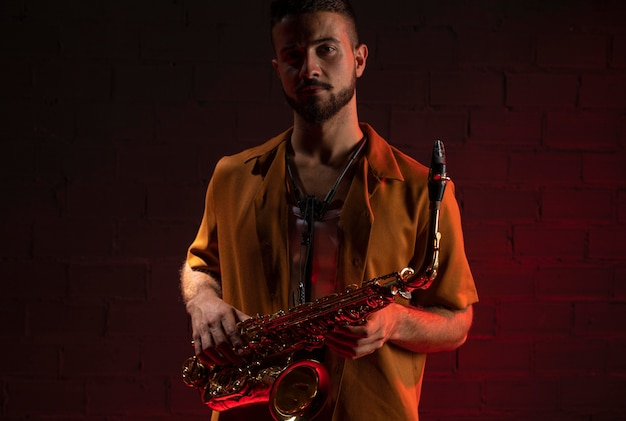 Vorderansicht des männlichen musikers, der ein saxophon hält