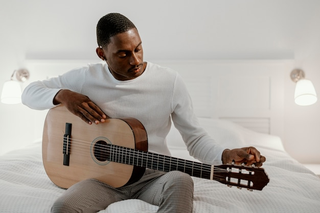Vorderansicht des männlichen musikers, der gitarre auf bett spielt
