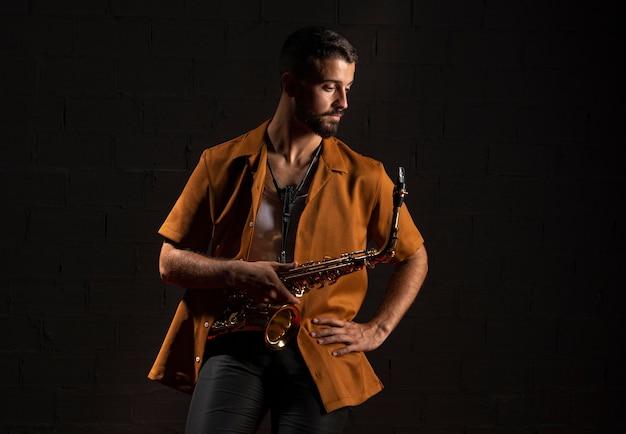 Vorderansicht des männlichen musikers, der mit saxophon aufwirft