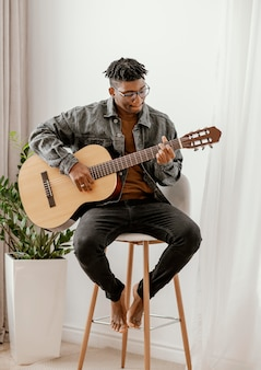 Vorderansicht des männlichen musikers, der zu hause gitarre spielt