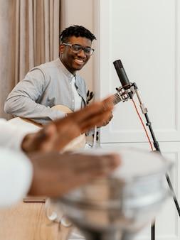 Vorderansicht des männlichen musikers zu hause, der gitarre spielt und singt