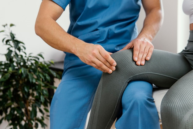 Vorderansicht des männlichen osteopathischen therapeuten, der das knie der patientin prüft