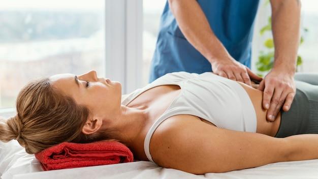 Vorderansicht des männlichen osteopathischen therapeuten, der den bauch der patientin prüft