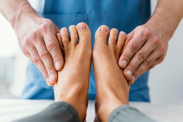 Vorderansicht des männlichen osteopathischen therapeuten, der die zehen der patientin prüft