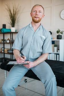 Vorderansicht des männlichen physiotherapeuten in der klinik mit zwischenablage
